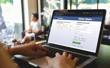Cafe-Besucher loggt sich mit Laptop bei facebook ein.